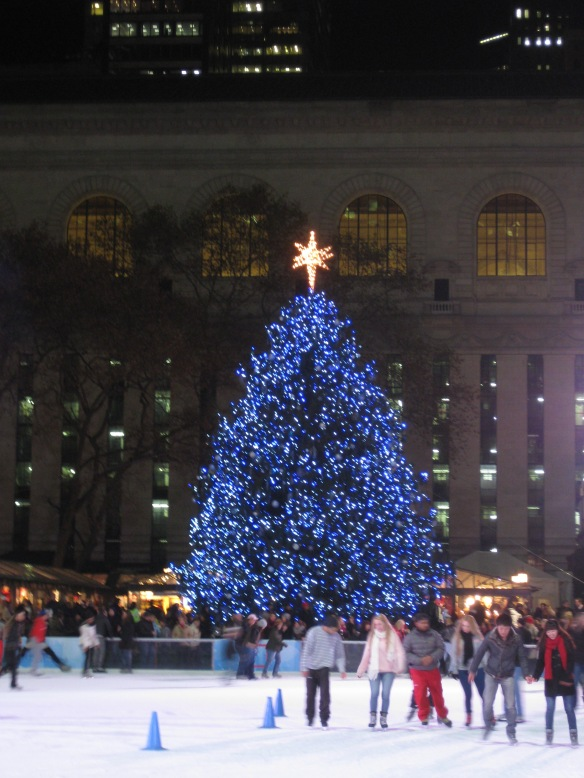 tree and ice rink in Bryant Park, NYPL in the background